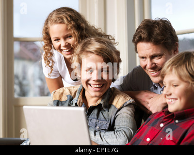 Father watching laptop with sons and daughter on sofa - Stock Photo