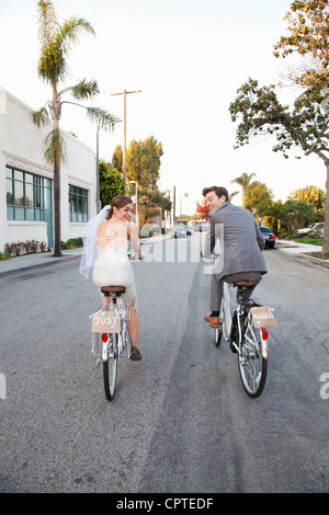 Young newlywed couple cycling along street, rear view - Stock Photo
