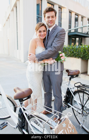 Portrait of young newlywed couple with bicycles - Stock Photo