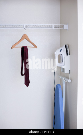 Tie on clothes hanger and iron in hotel wardrobe - Stock Photo