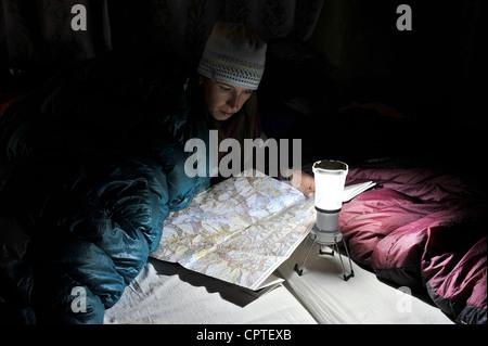 Woman in sleeping bag, looking at trail map, Yak Kharka, Nepal - Stock Photo