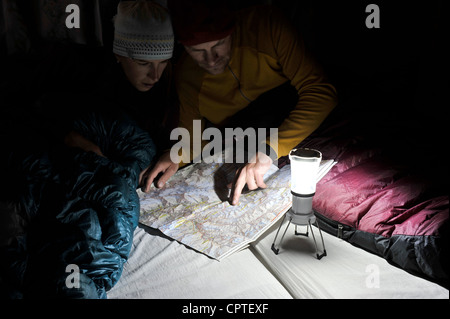 Couple in sleeping bags, looking at trail map, Yak Kharka, Nepal - Stock Photo