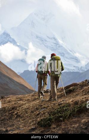 Trekker hiking a ridge in Thorung La, Nepal - Stock Photo
