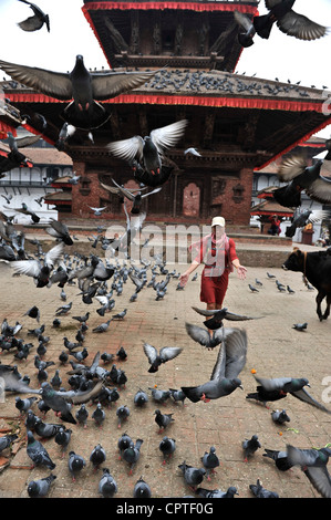 Woman running through a flock of pigeons in front of Jagannath Temple in Durbar Square of Kathmandu, Nepal - Stock Photo