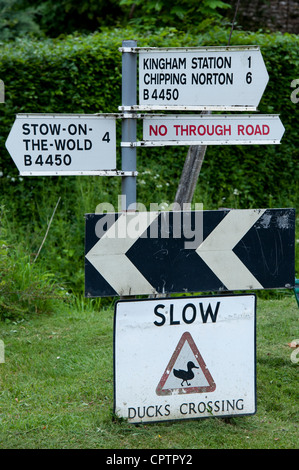 Slow Ducks crossing sign next to a road sign. Kingham, Oxfordshire, Cotswolds , England - Stock Photo