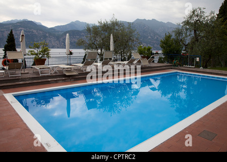 An empty swimming pool with the spectacular Lake Garda mountains backdrop in Malcesine Italy Lake Garda - Stock Photo