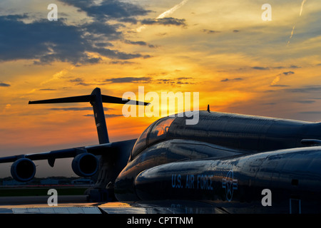 The sun sets on a United States Air Force T-38 and a C-17 aircraft at the 128th Air Refueling Wing, Wisconsin Air - Stock Photo