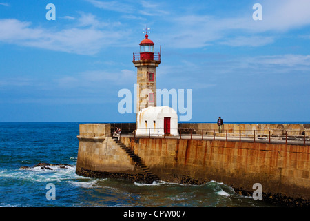 lighthouse on a pier on the Atlantic ocean coast in Porto, Portugal - Stock Photo