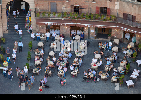 Aerial view from Il Torre, clock tower of diners at Bar Il Palio in Piazza del Campo, Siena, Italy - Stock Photo