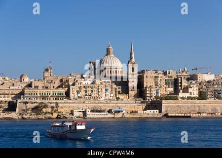 Tourist harbour cruise boat in front of Valletta skyline, Malta - Stock Photo