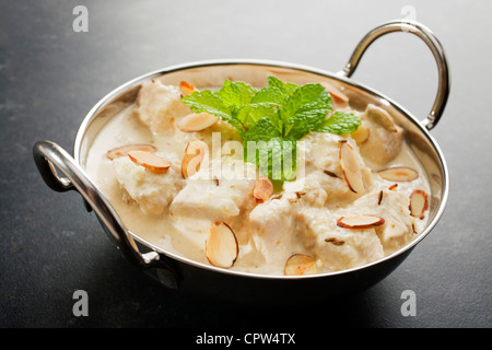 Mild and Creamy chicken korma, in a balti dish, garnished with mint, almonds and toasted cumin seeds, on a dark - Stock Photo