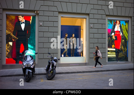 Stylish Italian woman walks past fashion displays of Guess Marciano casuals in Via de Pecori in Florence,Tuscany, - Stock Photo