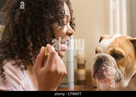 Young woman with treat in-hand speaking to her puppy dog - Stock Photo