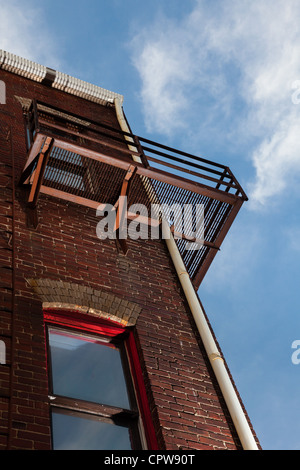 Metal fire escape ladder on old brick building from below - Stock Photo