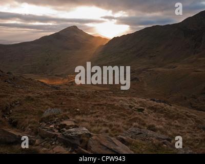Sun setting behind Yr Aran, a satellite peak of Snowdon viewed from the Watkin Path - Stock Photo