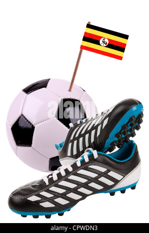 Pair of cleats or football boots with a small flag of Uganda - Stock Photo