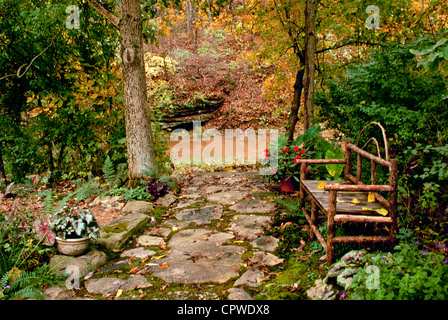 Beautiful even in fall: Shade garden with hand-built bench beside stream in autumn (series), Missouri USA - Stock Photo