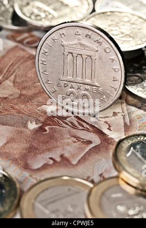 Greek drachma as coins and paper money. In the foreground € coins. - Stock Photo