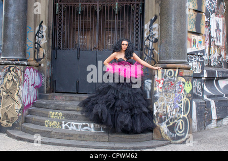 Model in evening dress poses in front of Germania Bank with graffiti on the Bowery in NYC, Jay Maisel studio home - Stock Photo