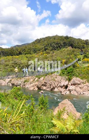 New Zealand, South Island, Abel Tasman National Park. People hiking over suspension bridge. - Stock Photo