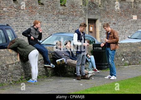 Youths hanging around in a group smoking and chatting with little else to do on a Saturday - Stock Photo