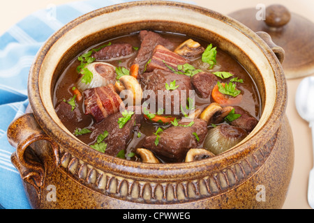 Classic beef bourguignon in a traditional brown pot. - Stock Photo