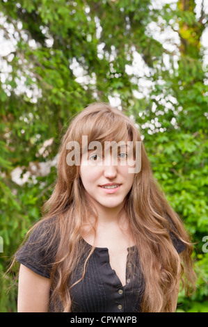 Portrait of beautiful young woman teenager with long blond hair brown eyes serious thoughtful expression outdoors - Stock Photo