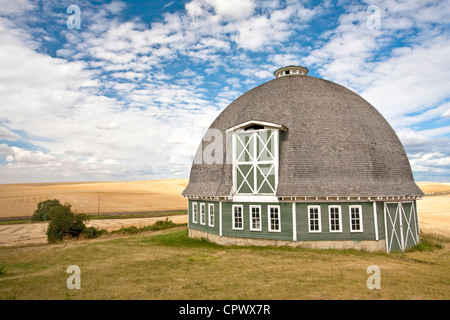 A scenic view of a round barn with a blue sky in the background. - Stock Photo