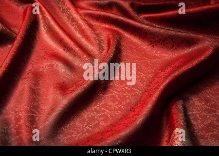 Red beautiful fabric background with folds - Stock Photo