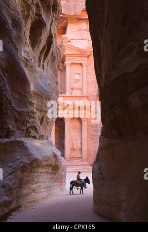 Tourists in Al-Siq leading to Facade of Treasury (Al Khazneh), Petra, Jordan (UNESCO World Heritage site) - Stock Photo