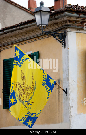 Flag of the Corso Contrada on flagpole in Asciano, in Tuscany, Italy - Stock Photo