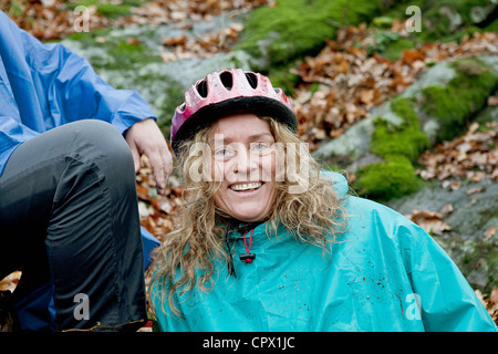 Mature woman resting from cycle ride in forest - Stock Photo
