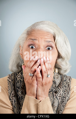 Portrait of senior woman covering mouth with hands in studio - Stock Photo
