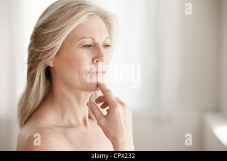 Mature woman touching chin - Stock Photo