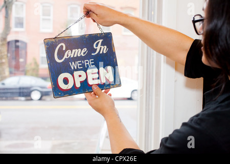 Man flipping over open sign in cafe - Stock Photo