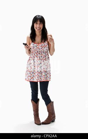 Smiling mature woman holding cellphone, studio shot