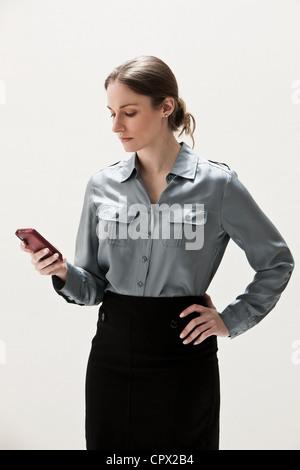 Young businesswoman using cellphone, studio shot - Stock Photo