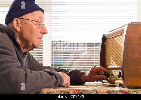 Senior man tuning radio, close up - Stock Photo