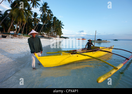 fisherman launching a boat on San Juan Beach at dusk, Siquijor, The Visayas, Philippines - Stock Photo