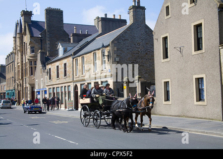 Kirkwall UK Tourists in a horse drawn carriage on a tour of this historic town, capital of the Orkney Islands - Stock Photo