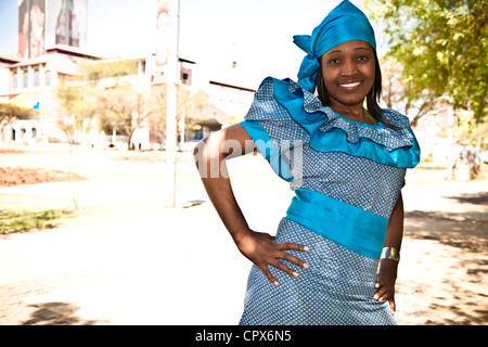 African woman dressed in traditional clothing smiles at the camera - Stock Photo