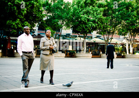 Two people walking in Nelson Mandela Square, Sandton, South Africa - Stock Photo