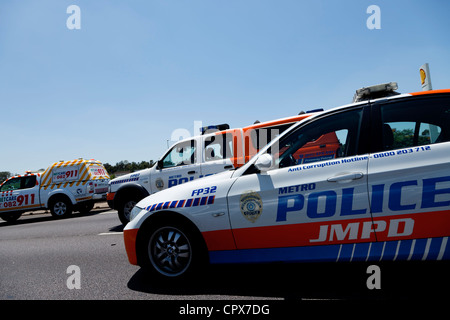 Johannesburg Metro Police Department cars driving in formation on a public road - Stock Photo