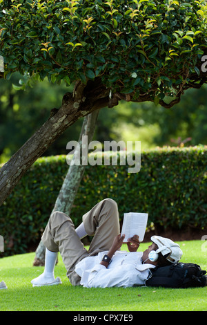 African man lying on grass, reading a book while listening to music - Stock Photo