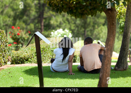 Young African couple sitting on grass, looking at a view - Stock Photo