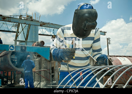 Black factory worker welding steel frame - Stock Photo