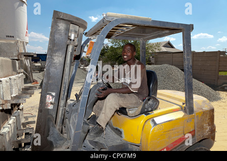 African construction worker drives a forklift in a construction yard - Stock Photo