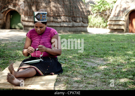 African woman dressed in traditional clothing sits on floor, creating beadwork - Stock Photo