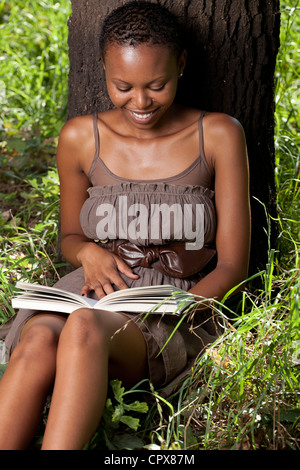 Young adult funky black female sitting against a tree, reading a book - Stock Photo