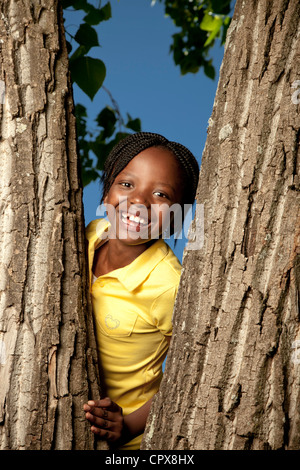 Portrait of a little girl standing in a tree - Stock Photo